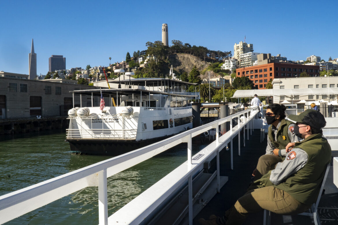 Two National Park rangers wait on the dock before boarding a ferry to work on Alcatraz.