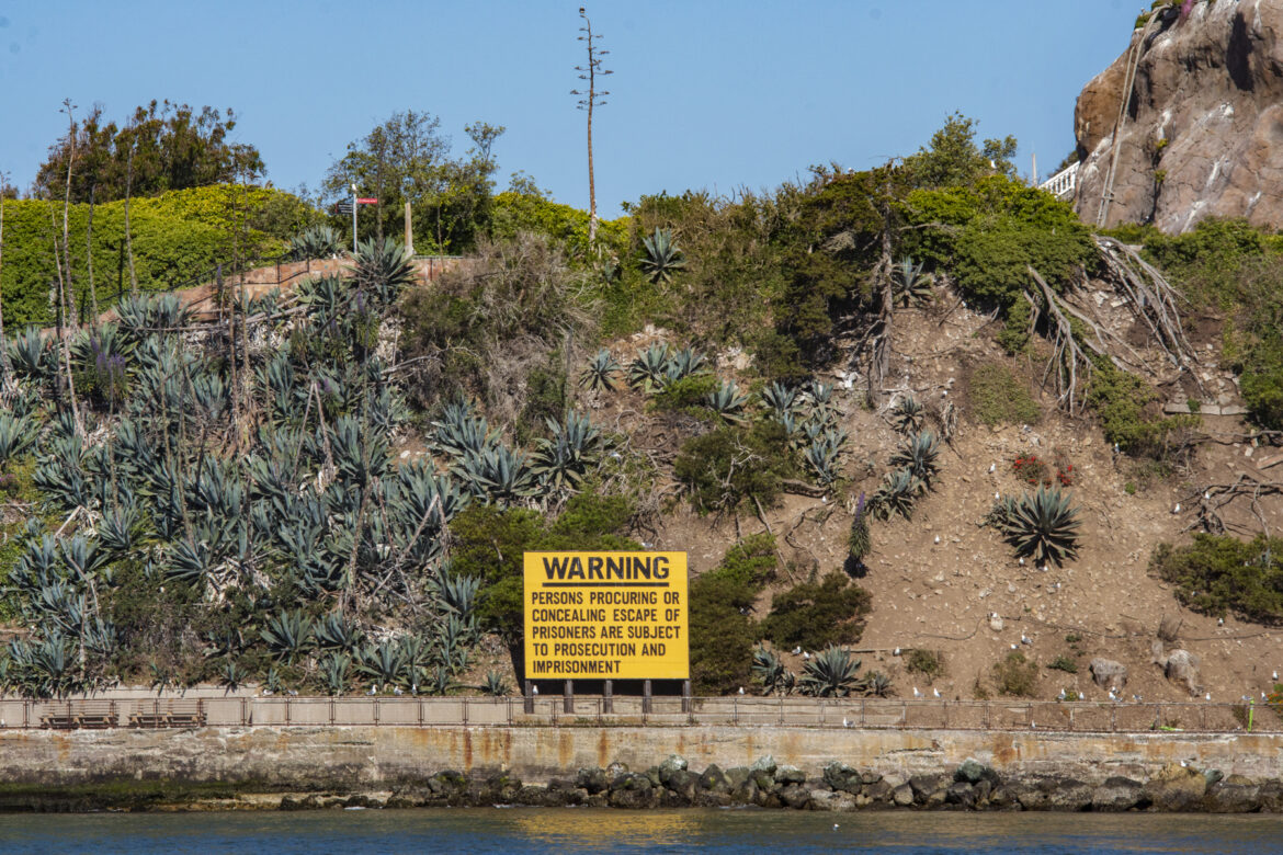 """A yellow warning sign from Alcatraz's prison era on the agave trail cautions that visitors """"concealing escape of prisoners are subject to prosecution and imprisonment."""""""