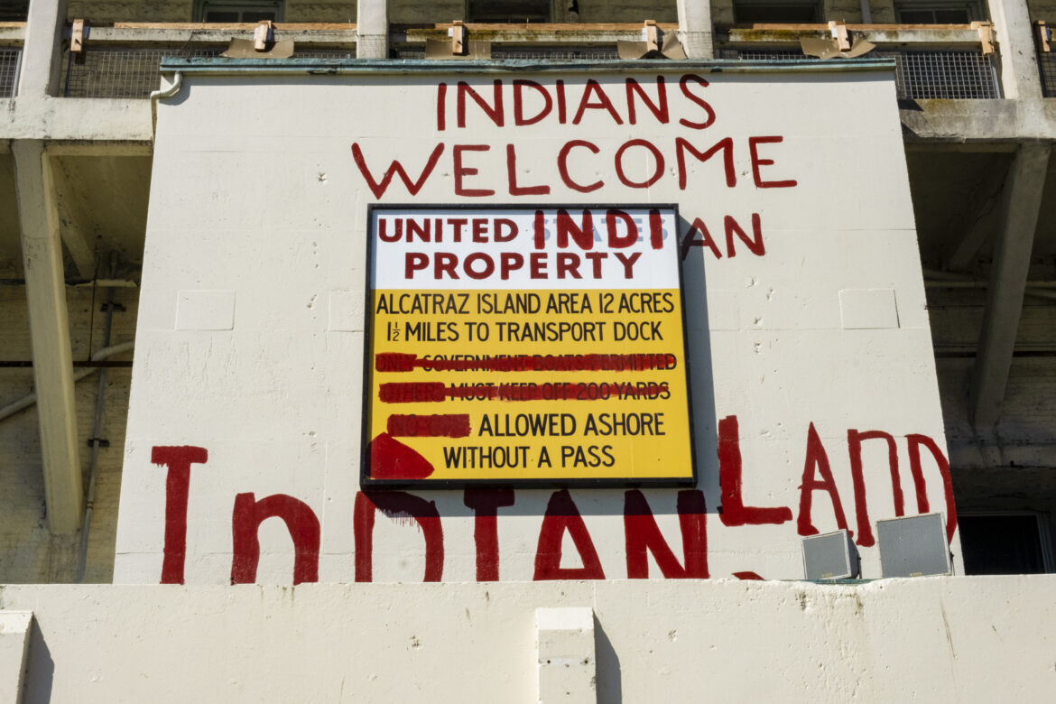 """A former penitentiary sign is modified with red paint to display this text: """"Indians Welcome. United Indian Property. Alcatraz Island. Area 12 acres. 1 ½ miles to transport dock. Allowed ashore without a pass. Indian Land."""""""