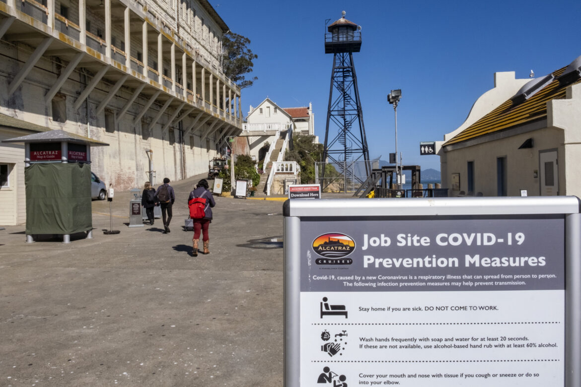 National Park employees arrive on Alcatraz, walking past historic buildings, to prepare the island for the day's visitors. There is a COVID-19 protocol sign in the foreground and a water tower in the background.