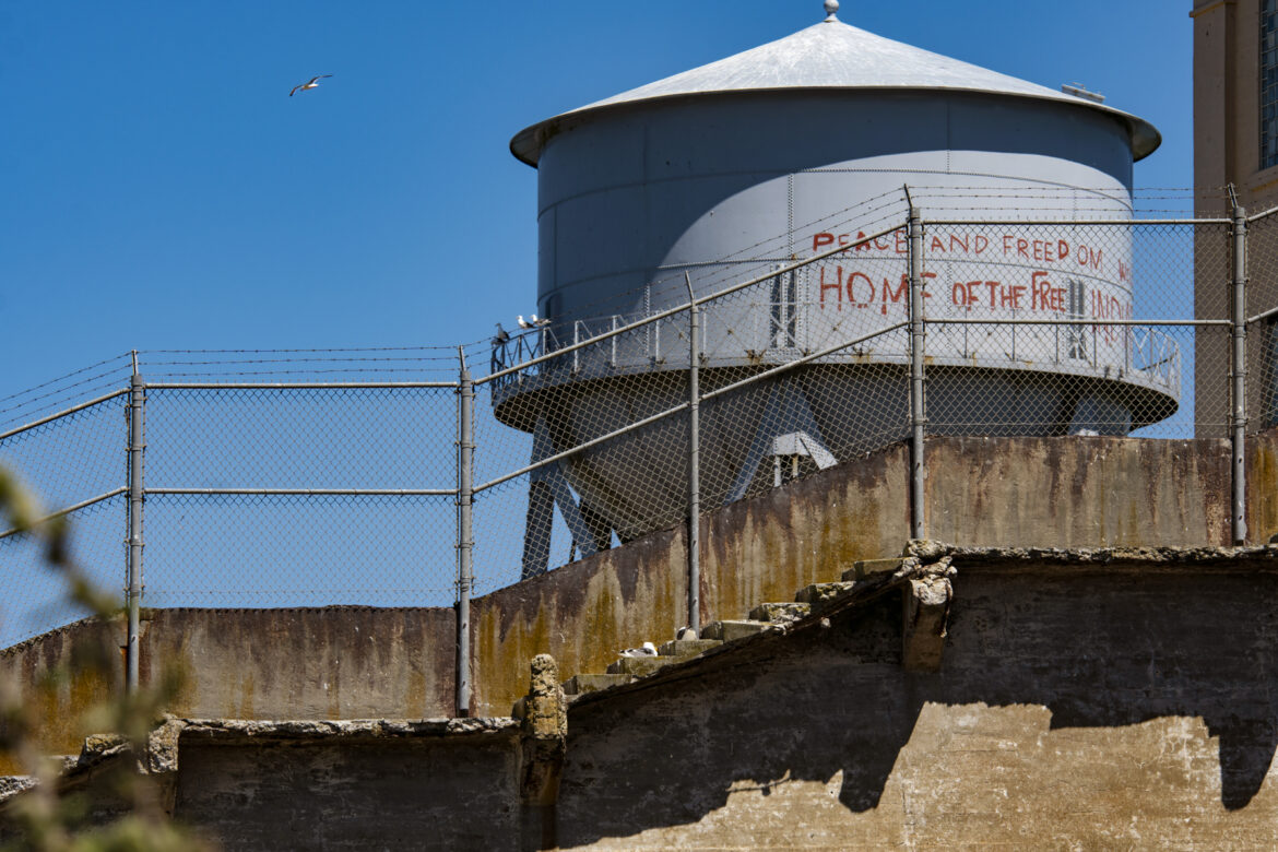 """Red paint on a water tower reads: """"Peace and Freedom. Home of the Free. Welcome to Indian Land."""""""
