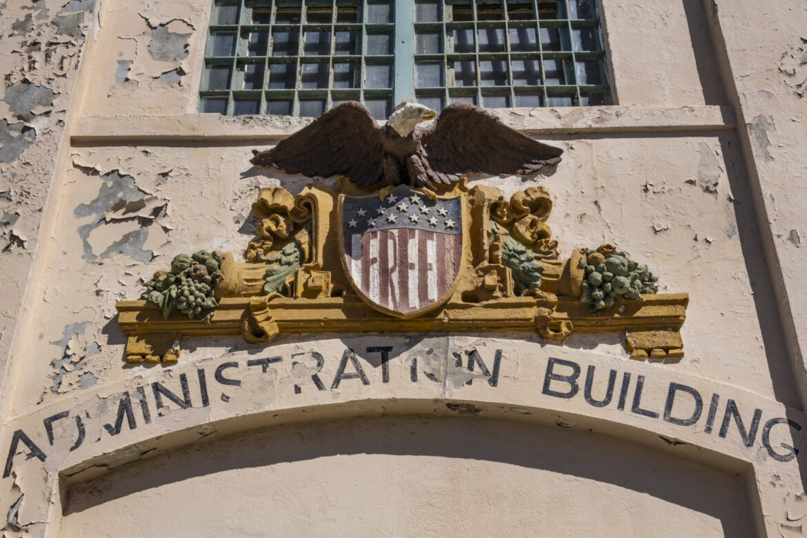 """Eagle Plaza, the entrance of the cell house building, features a Bald Eagle above a shield, which occupiers repainted with the word """"Free."""""""