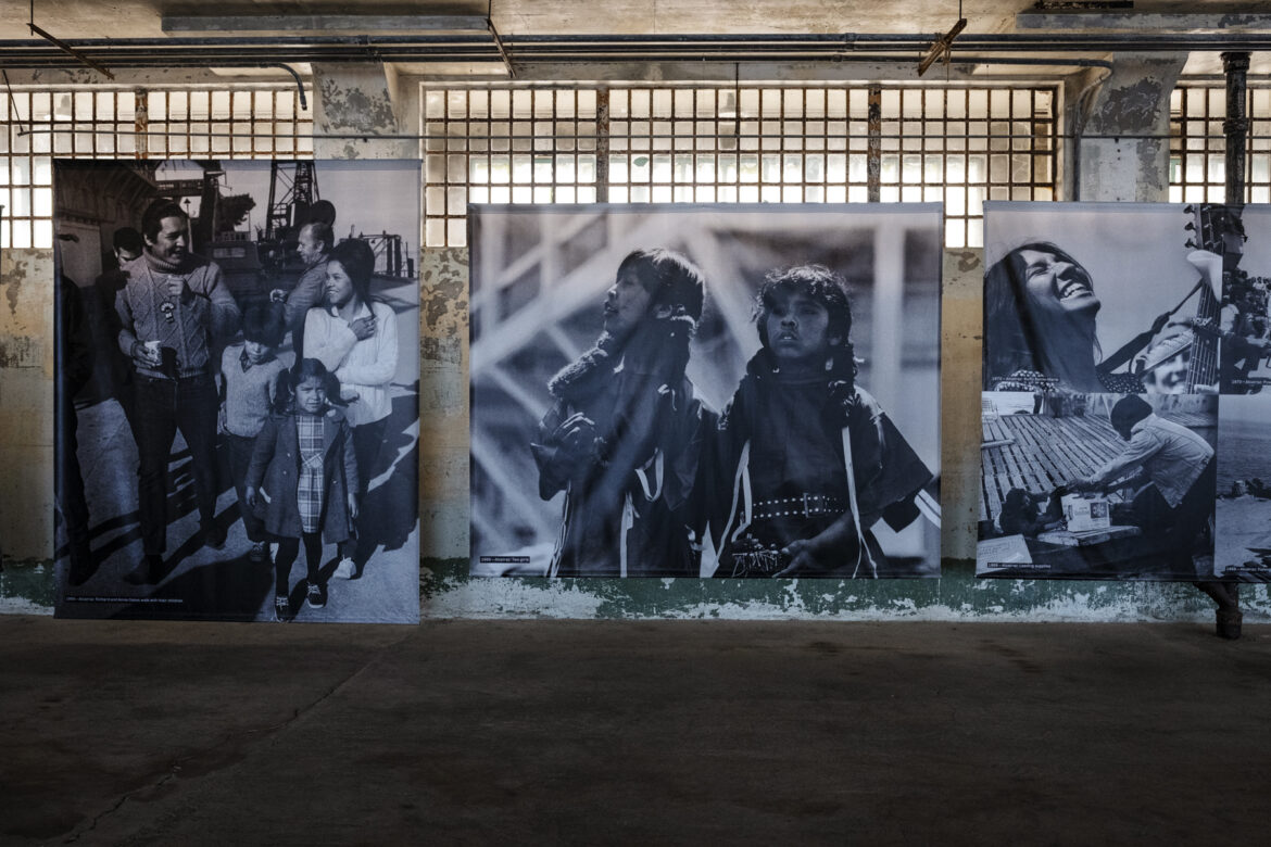 Large photos on canvases depict young families and children on Alcatraz during the occupation.