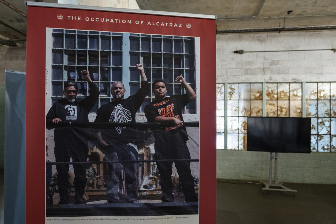 """A portrait of former occupiers Eloy Martinez and Darren Laiwa with the grandson of Richard Oakes, who was a leader in the occupation, raising their fists after they repainted the word """"FREE"""" on the shield at Eagle Plaza."""