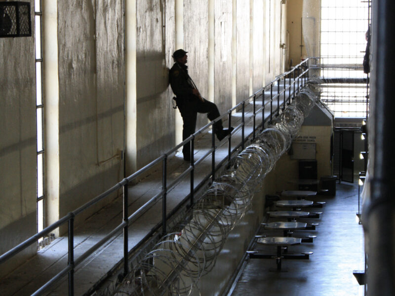 A prison guard stands inside a hall at San Quentin State Prison, his leg up on a railing fortified with razor wire, overlooking the ground floor.