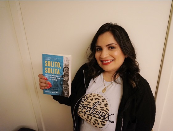 A woman stands against a wall holding a copy of Solito, Solita, a book about border-crossing youth.