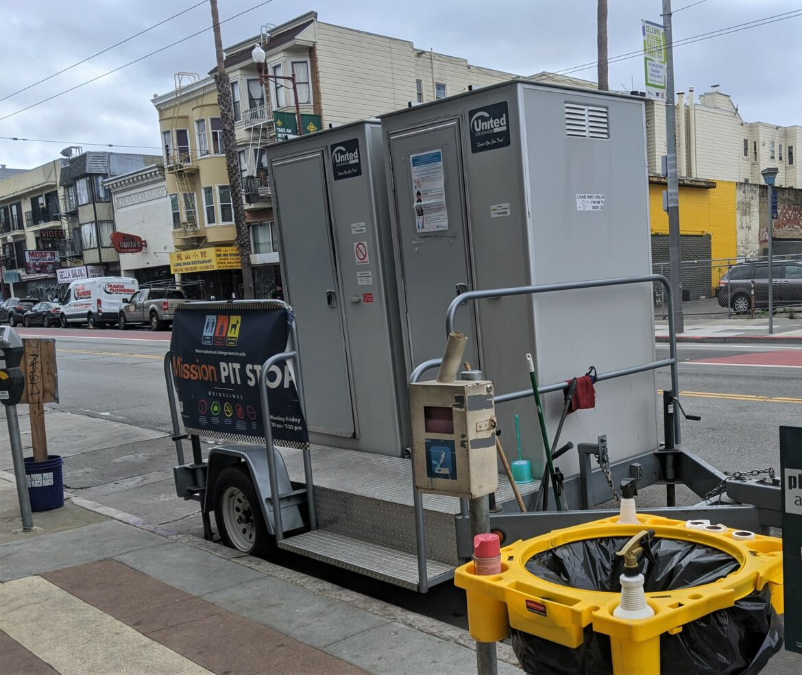 Two toilets sit on a movable trailer on a street in San FRancisco's Mission District.