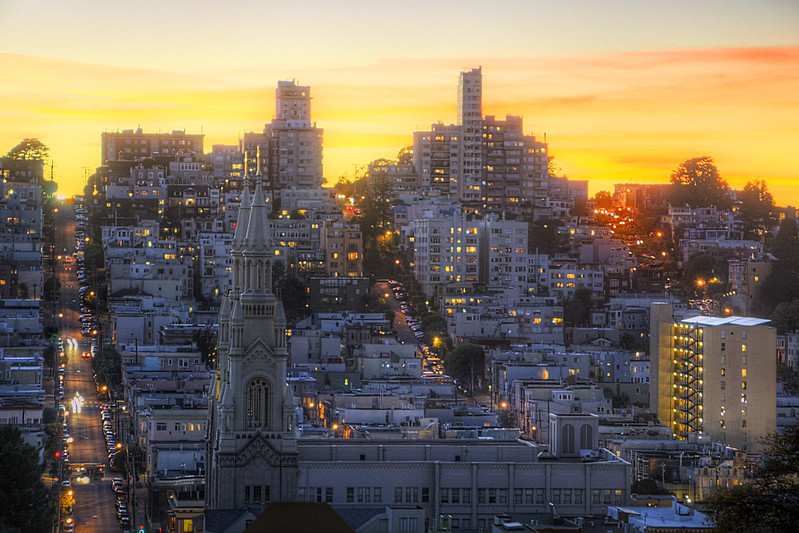 A view of San Francisco's Russian Hill neighborhood, set against a yellow sunset.