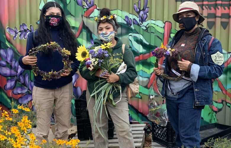 Three people stand and hold flowers and other harvest from Hummingbird Farm.