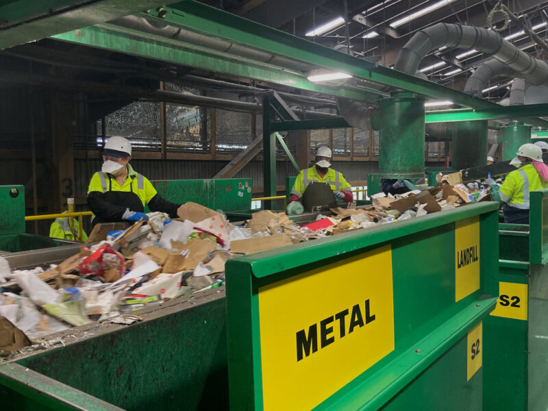 Workers at the initial sort deck inside Recology's sorting facility at Pier 96 in San Francisco pluck items that cannot be recycled or pose a threat to equipment from a conveyor belt.