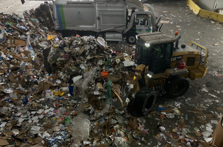 A worker loads material to be sorted into a drum feeder that will transport it into the system at a constant rate, as a sanitation worker unloads a recycling truck onto the tipping floor. Recology processes about 500 tons of material daily at the Pier 96 facility.