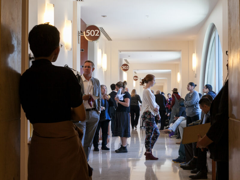 More than a dozen people stand in a hallway leading to courtrooms in San Francisco.