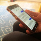 """Someone's hand is shown holding a phone with text messages on the screen. San Francisco residents who text """"Rent"""" to 1-888-732-3215 will receive information about the statewide eviction moratorium, as well as referrals to groups that help people request financial aid to repay rent and utility debt."""