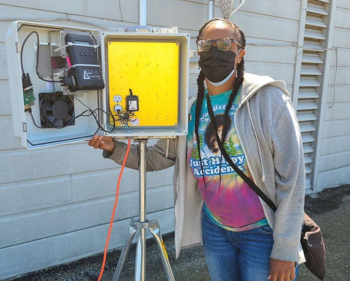 Volunteer Tiffany Williams displays an open box filled with electrical air monitoring equipment.