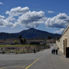 Several men gather just outside a building at San Quentin prison, with Mt. Tamalpais framed by dramatic clouds in the background. Four prisoners a tSan Quentin have tested positive for COVID-19 and their housing unit is under quarantine.