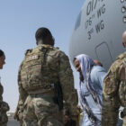 Evacuees from Afghanistan arrive at Ali Al Salem Air Base, Kuwait, on an aircraft crewed by Air National Guard members on Aug. 23, 2021.