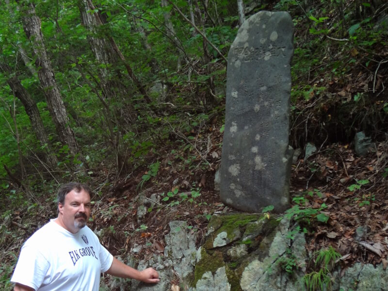 """Rick Wilson stands in front of a 1930s-era """"tsunami stone"""" in Aneyoshi Bay, Japan, that warns residents not to live below its elevation at 150 feet in August 2011. The tsunami that hit Japan that year flooded areas of up to 130 feet in elevation. Because they heeded the warning of the stone, the people in this community were safe, Wilson said."""