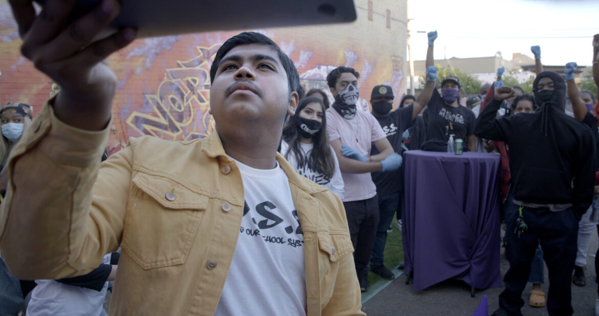"""Still from """"Homeroom"""" in which student Denilson Garibo holds up a laptop to point the webcam at a group of people behind him."""