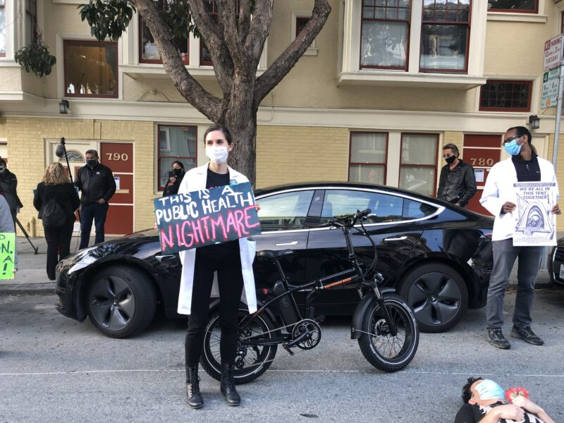 """Two doctors protest outside Mayor London Breed's house on April 30, 2020, calling for more hotel rooms to be opened for people experiencing homelessness to safely shelter during COVID-19. The one in front holds a sign reading """"this is a public health nightmare."""""""