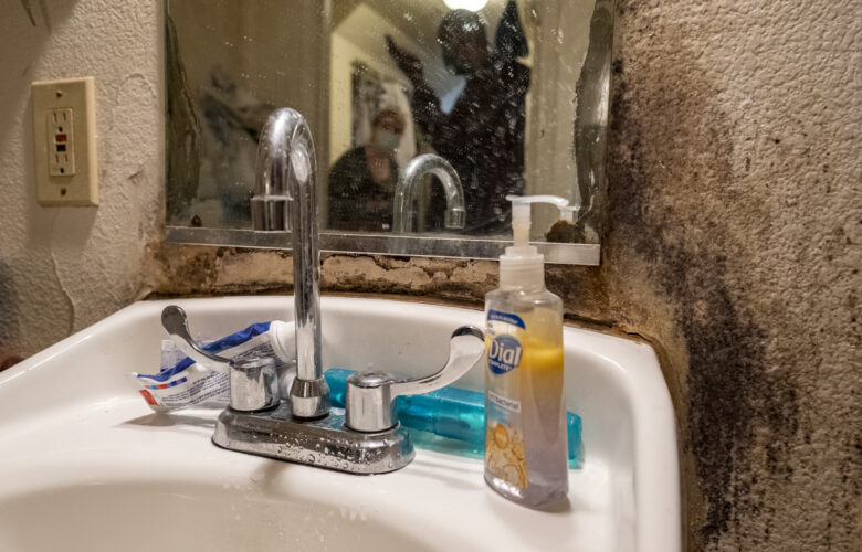 The wall behind a bathroom sink is marred by black mold.