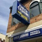 """A """"check cashing"""" sign hangs above a storefront. While San Franciscans who owe COVID-19-related rent debt are eligible for relief from the government, those who borrowed from friends, family, and other sources are stuck with that debt."""